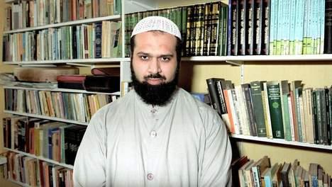 Met een zelfingenomen en zelfgenoegzame duivelse blik kijkt nep imam Haselhoef in de Camera